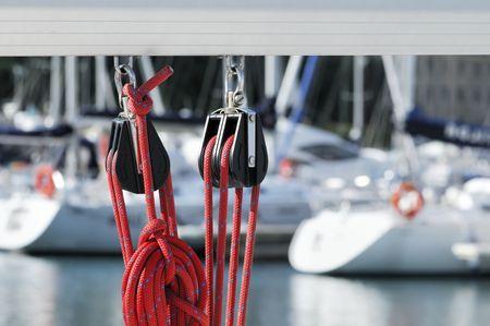 pulleys: Close-up de la vela poleas con cuerda de color rojo sobre un boom con los barcos de un puerto deportivo en el fondo