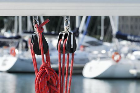 Close-up of sailing pulleys with red rope on a boom with boats of a marina in