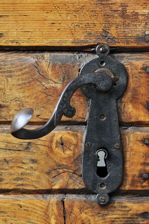 handles: Close-up of an old iron handle on a wooden front door Stock Photo