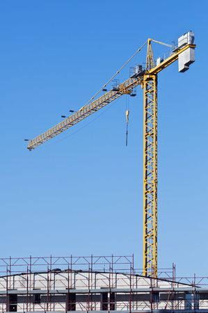 Yellow crane in a contruction site abd a building with scaffolding
