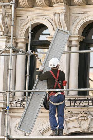 Workman putting up scaffolding