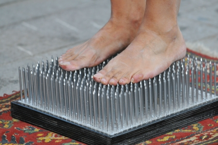 Fakir foots standing on a nails bed Stock Photo
