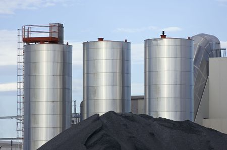 stocked: Metallic silos with stack of ground of an industrial plant Stock Photo