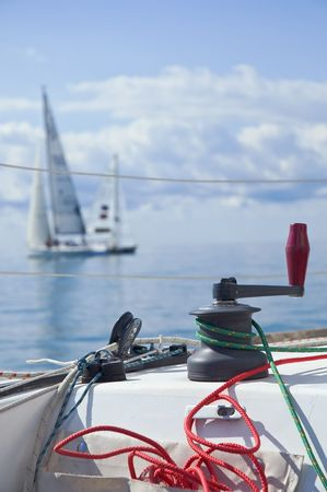 Ropes and navigation tools in foreground with two sailboats in background