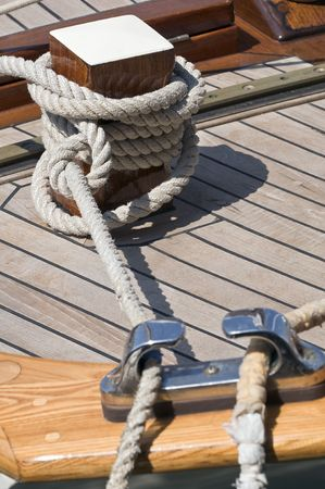 Detail of a wooden boat with rope tied up on a bitt Stock Photo