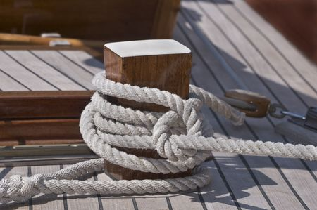 fasten: Close-up of a rope fasten to a wooden bitt Stock Photo