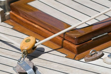 Detail of block and rope on a deck of a wooden sailboat