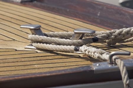 Ropes tied up on a bitt of a wooden boat