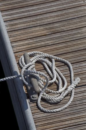 Tied up rope on a cleat of a pier Stock Photo