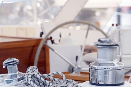 Detail of sailboat with winches, rope and  steering wheel photo