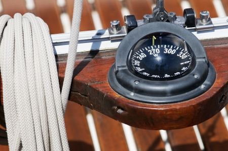 Compass indicating direction on a wooden sailboat