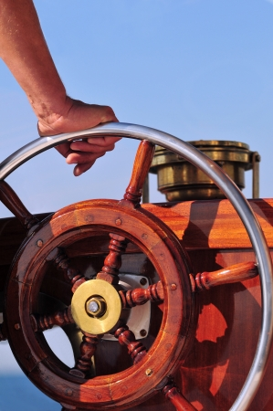 Hand holding a wooden yacht steering wheel
