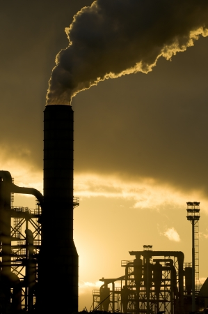smoke stack: Sunset silhouette of industrial plant Stock Photo