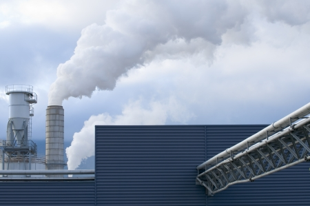 Detail of a modern industrial building with pipes, chimeys and smoke