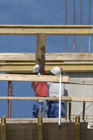 Two carpenters preparing framework to lay a new floor in a building under construction