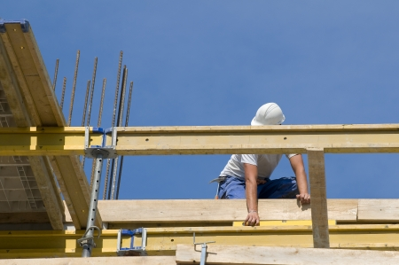Worker controlling the level of wooden framework in a building under construction