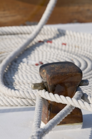 Detail of a sailboat deck with two ropes tied up on a bitt and one rolled rope  Stock Photo