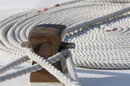 Deck detail of a docked boat with two ropes on a bitt and another one rolled