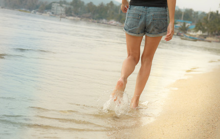 populate: Girl in jeans shorts walking in the water along the beach.
