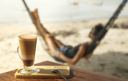 Cup of coffee on a table, in the background a woman in a hammock enjoying a view of the sea.
