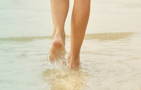 belles jambes: nice legs of a pretty girl walking in water. Banque d'images