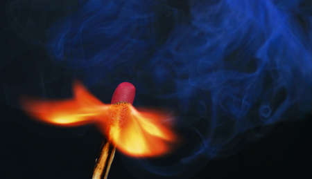 Photo of a burning match with smoke on a black background photo