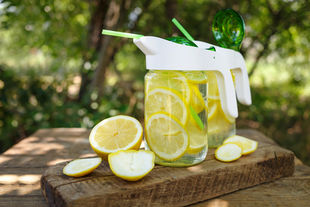 Two jars of homemade lemonade on a wooden board outdoors.