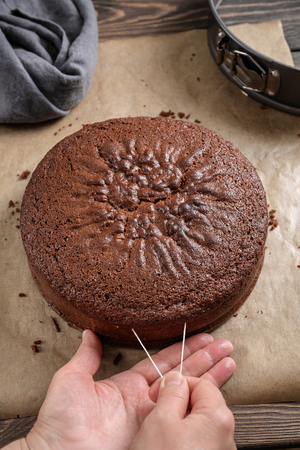 Steps in making chocolate cake. Women's hands slices the cake with culinary thread Stockfoto