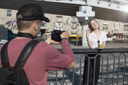 Photographer shoot a beautiful girl at the camera Фото со стока