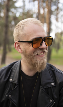 Portrait hipster young guy with a beard and mustache with sunglasses
