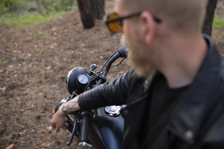 Portrait hipster young guy with a beard and mustache with sunglasses, street casual a motorcycle