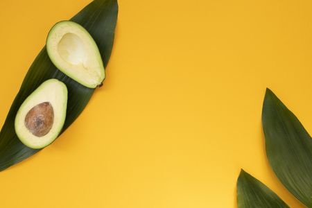 Ripe sliced avocado on bright yellow background top view flat lay. Tropical summer abstract background with avocado