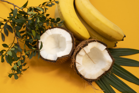 Yellow background with bananas, coconuts and leaf 스톡 콘텐츠
