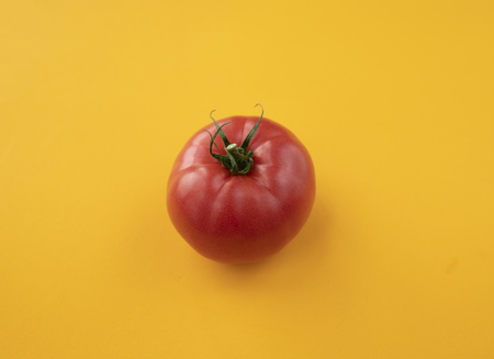 Close up ripe tomato on bright yellow background top view flat lay. Summer abstract background with tomato