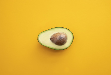 Close up ripe sliced avocado on bright yellow background top view flat lay. Tropical summer abstract background with avocado