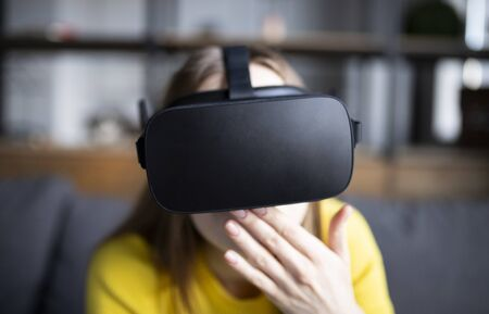 Cute girl plays the game on the console. Happy young woman using a virtual reality headset