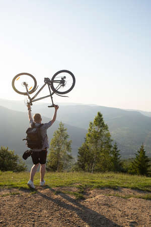 A young guy raises a bicycle in his hands against a background of sky, mountains and sunset