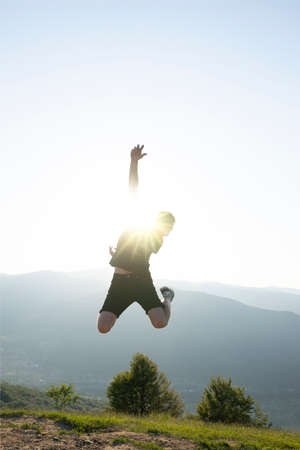 Young guy jumping on the background of beautiful mountains with a sun glare