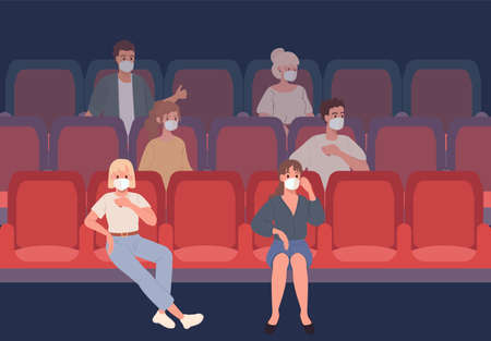Young People sitting in the cinema in protective masks observe social distance