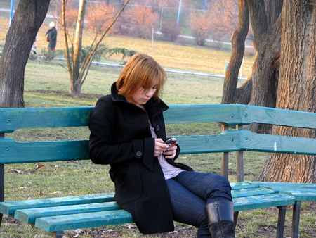 Writing an sms on a bench in a park Stock Photo