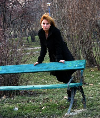 a beautiful girl supported by a bench