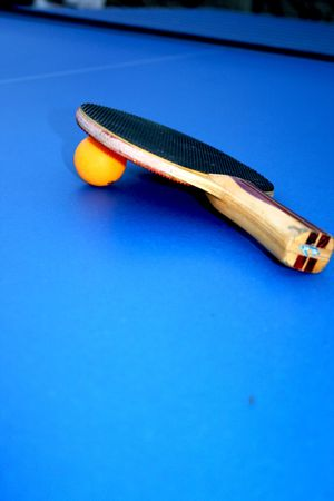 Table tennis pallet and an orange ball on a blue table