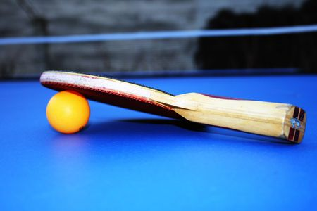 the tennis bat and a ball on a tennis table.