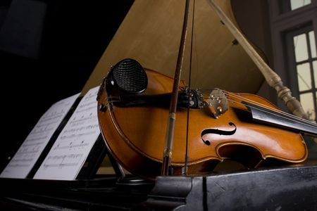 viola: Violin on grand piano with notes sheets Stock Photo