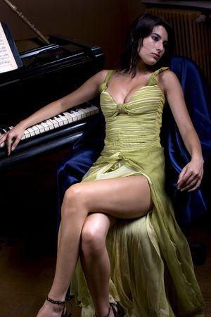 a beautiful attractive girl posing near a piano photo