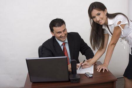 secretary showing something to her boss photo