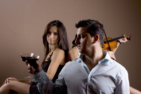 violin making: a woman and a man making a toast, an a girl in background playing at a stradivarius violin