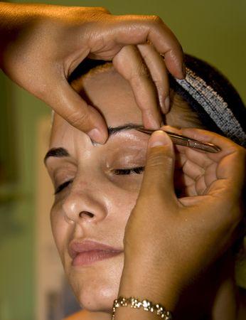 tweezing eyebrow: girl tweezing eyebrow at cosmetic