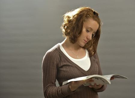 red haired girl: beautiful red haired girl reading a magazine