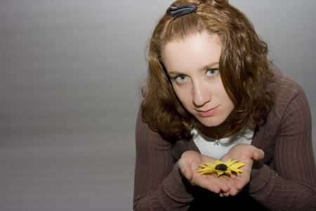 portrait of a beautiful redhaired girl holding a yellow flower in her hands photo